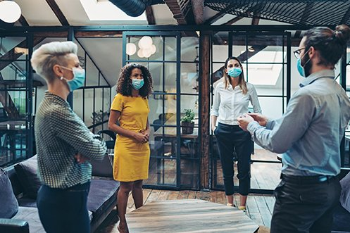 : Four coworkers wearing masks in a shared office space, three women and one man, talking about the top 5 COVID-19 risks for their company's relocation policy
