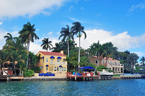 Beautiful house with yellow siding, blue awnings, palm trees, and a boat dock that has risen in value as Florida gains residents