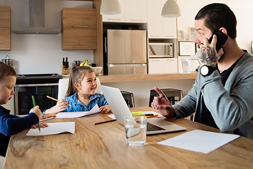 Man with dark hair and beard, wearing a gray sweater and large wristwatch, talking on a cell phone, sitting at kitchen counter, working on a laptop computer, working from home with kids, one boy and one girl sitting across from him, smiling