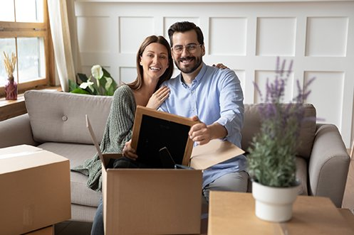 Woman with long dark hair and wearing a green sweater, man with dark hair, mustache, and beard wearing glasses and a blue shirt, both sitting on a couch, smiling, unpacking a box in their new home after their relocation mortgage application was approved