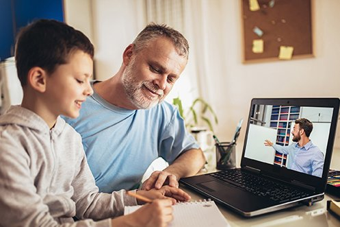 Father with mustache and beard, wearing a blue shirt, son with dark hair, wearing a gray pullover, both watching a virtual tutoring session on a computer, as the father helps the son with the lesson