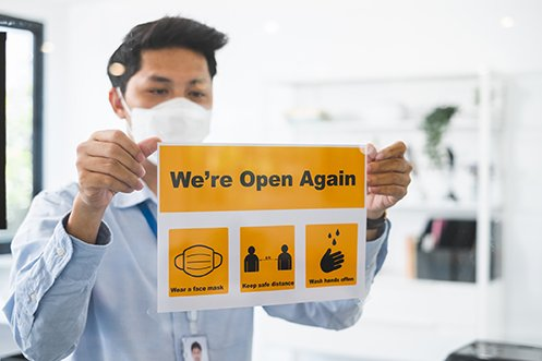 Man with dark hair, wearing a face mask, hanging a sign in a window saying the business is open again as employees return to workplaces safely