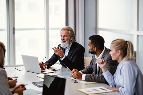 Man with gray hair and beard, wearing jacket, in front of open laptop, holding eyeglasses and gesturing with one hand; man next to him, with dark hair, wearing a jacket, looking at the man with gray hair; woman with blonde hair wearing blue shirt, holding a pen; all are Relocation Department team members sitting at a meeting table in a conference room, all wearing business professional attire, planning future global relocations and discussing pre-decision tax planning to reduce global tax obligations
