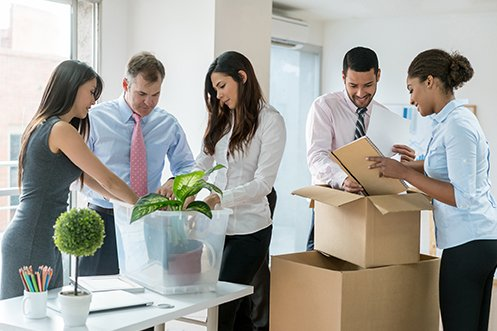 Five employees, three women and two men, all in business attire, unpacking boxes in their new office after they created a 2021 business relocation budget to help them move from California to Arizona