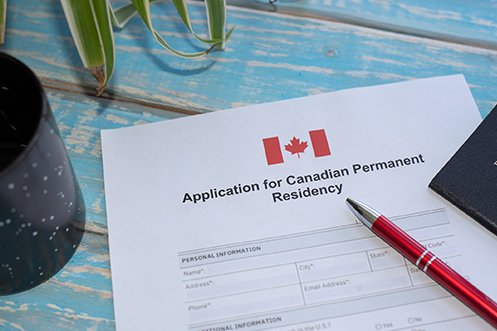 Canada citizenship path expanding and will allow temporary residents to more easily apply for permanent residency with the application shown on a table, with a pen ready for filling out the paperwork