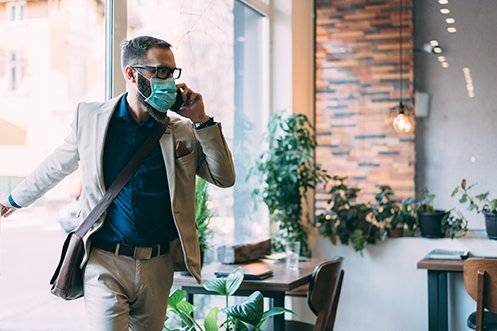 Business man with dark hair and beard wearing a mask, eyeglasses, and a business jacket, talking on a phone, entering one of his employer's future workplaces post-COVID-19