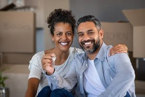 Woman with dark hair, wearing white polka dot shirt, smiling, and man, wearing blue shirt and white t-shirt, smiling, both facing forward, woman has her arm around man's shoulder, man holding keys to their new home which they bought during the 2021 housing market