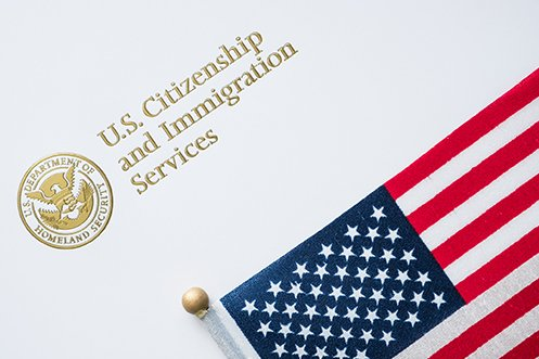 White USCIS envelope with gold lettering in upper left corner and American flag, representing the organization that will choose H-1B visa registrations based on prevailing wage levels