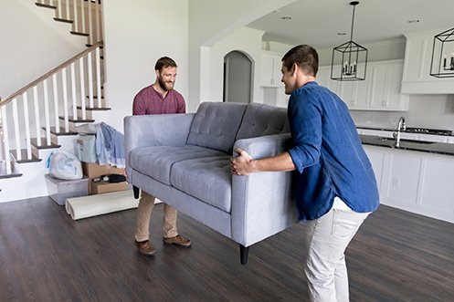 Two men, one with beard and wearing a red shirt, other wearing a blue short, former California residents move a sofa into their new home in Nevada