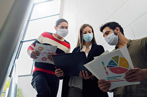 Three employees holding a laptop and charts, all wearing face masks, two women and one man, discussing the benefits of relocation program outsourcing