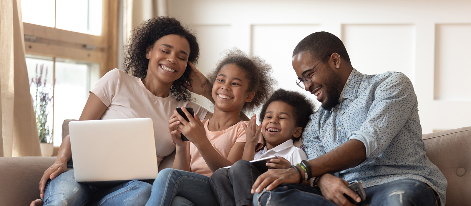 family laughing while looking at laptop